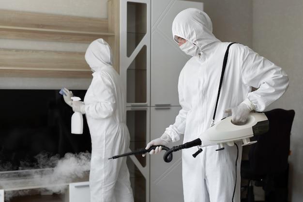 Dezynfekcja koronawirusem. ludzie w hazmatach dezynfekujący w mieszkaniu, w przestrzeni kopii, dezynfekujący gorącą parą