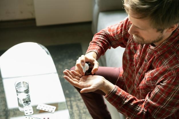 Dezynfekcja rąk. kaukaski mężczyzna przebywający w domu podczas kwarantanny z powodu koronawirusa, rozprzestrzeniającego się covid-19. staram się spędzać czas pożytecznie i przyjemnie. pojęcie opieki zdrowotnej i medycyny, izolacja.