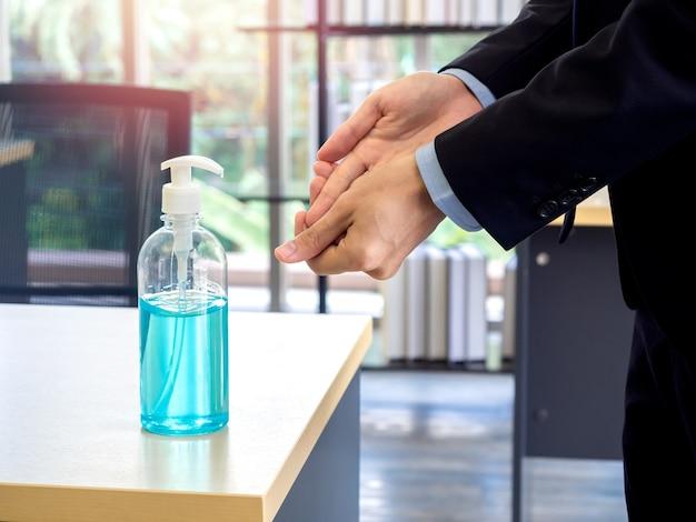 Dezynfekcja rąk żelem alkoholowym. ręce biznesmena za pomocą środka odkażającego na stole w biurze