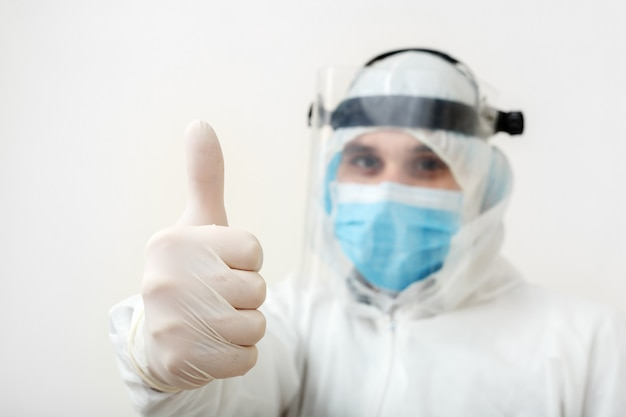 Dezynfektor lub lekarz ubrany w strój ochronny i maskę pokazującą kciuki do góry, pozytywny gest. podobnie jak koniec epidemii pandemicznej covid-19, koronawirus, kwarantanna. pojęcie medycyny opieki zdrowotnej