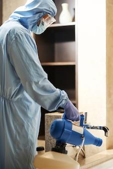 Dezynfektor w kombinezonie ochronnym i maska rozpylająca środki dezynfekujące w hotelowej łazience. koncepcja koronawirusa i kwarantanny