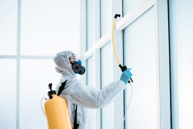 Dezynfektor w kombinezonie ochronnym rozpyla środek dezynfekujący w pomieszczeniu