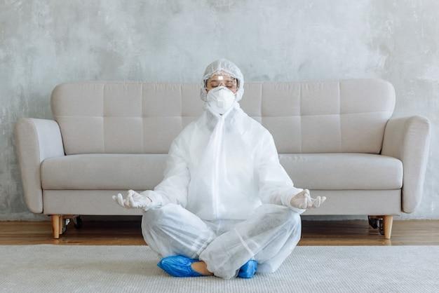 Dezynfektor w kombinezonie ochronnym w domu w pokoju siedzi w pozycji lotosu przed sofą. koncepcja pandemicznej dezynfekcji koronawirusa lub covid-19. dezynfekcja domu