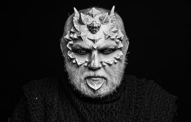 Diabeł na czarnym tle. kosmiczny lub gadzi makijaż z ostrymi cierniami i brodawkami. koncepcja horroru i fantasy.