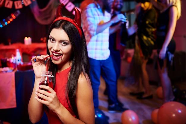 Diabeł pani pozuje na imprezie, pije coś