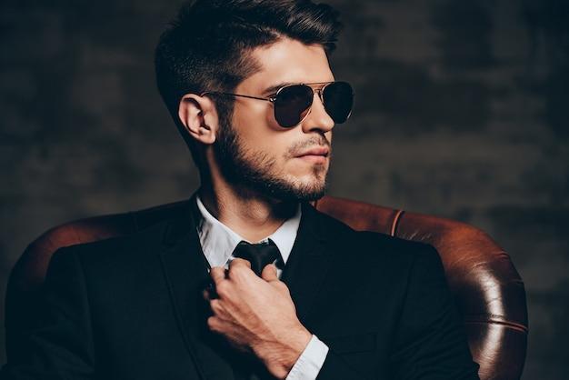 Diabeł tkwi w szczegółach. portret młodego przystojnego mężczyzny w garniturze, poprawiając krawat i odwracając wzrok, siedząc w skórzanym fotelu na ciemnoszarym tle