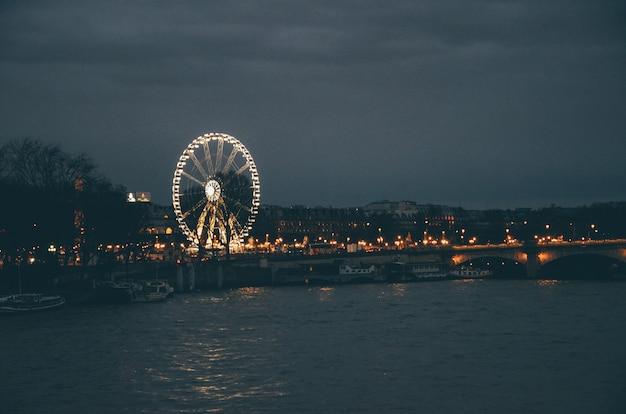 Diabelski młyn otoczony rzeką i budynkami pod zachmurzonym niebem nocą w paryżu
