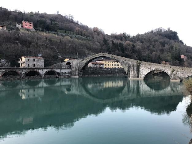 Diabelski most otoczony wzgórzami porośniętymi lasami odbijającymi się w jeziorze w borgo a mozzano