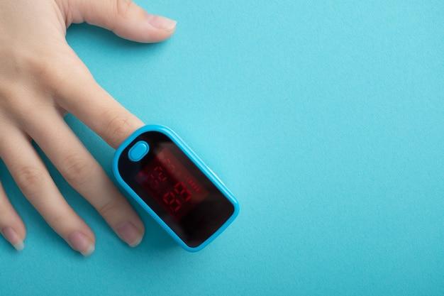Diagnostyka chorób układu oddechowego. kobiecy palec w pulsoksymetrze na niebieskim tle z copyspace