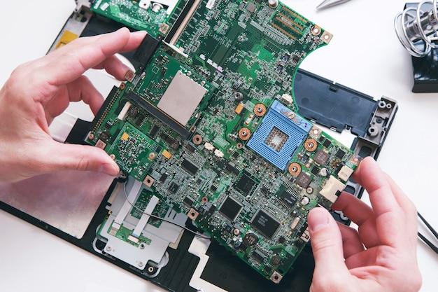 Diagnostyka, naprawa, koncepcja obsługi laptopa. płyta główna z komputera, pc w warsztacie widok z góry