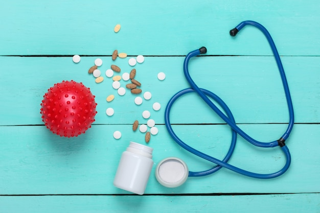 Diagnoza koronawirusa, zapalenie płuc. stetoskop ze szczepem wirusa, tabletki na niebieskim drewnianym