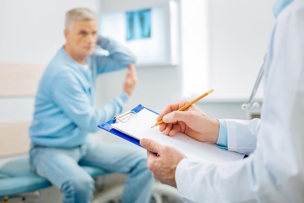 Diagnoza medyczna. selektywne skupienie się na notatkach lekarzy zapisywanych w pokoju medycznym podczas stawiania diagnozy