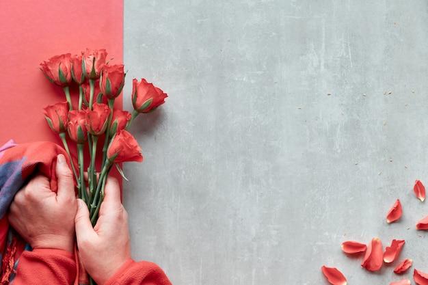Diagonalna geometryczna papierowa ściana na kamieniu. płasko leżące, kobiece dłonie trzymają czerwone róże i żywy modny kolorowy szal, rozproszone płatki. widok z góry, koncepcja na walentynki, urodziny lub dzień matki.