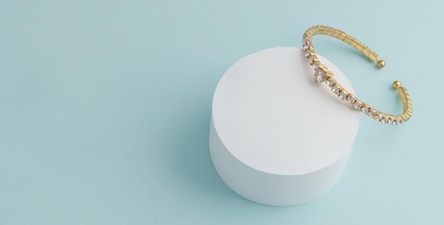 Diamentowa złota bransoletka na białej round platformie na błękit ścianie z kopii przestrzenią