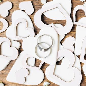 Diamentowe obrączki na białych kształtach serca wycięte
