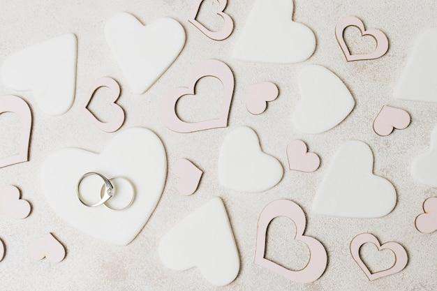 Diamentowe obrączki ślubne na białym i różowym kształcie serca nad betonowym tłem