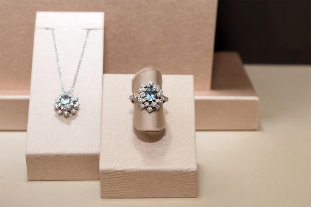 Diamentowy pierścionek i naszyjnik z niebieskimi szlachetnymi klejnotami. biały złoty pierścionek na stojaku. modne luksusowe akcesoria
