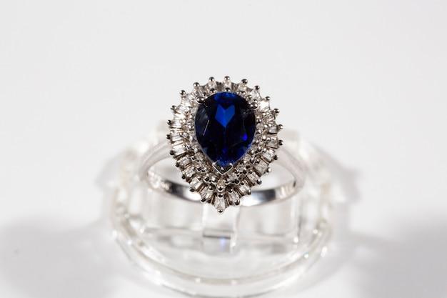 Diamentowy pierścionek. pierścionek z brylantem z szafirem na białym tle. pierścionek z brylantami i dużym szafirem. złote obrączki ślubne.