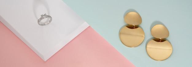 Diamentowy pierścionek z białego złota i para kolczyków na pastelowym tle