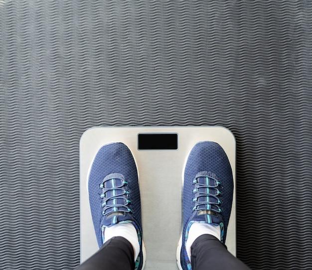 Dieta i utrata wagi. widok z góry kobiecych stóp w butach sportowych stojących na wadze