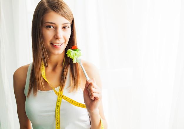 Dieta i zdrowe odżywianie. młoda kobieta je zdrowej sałatki po treningu