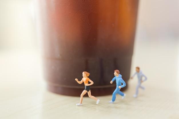 Dieta, jedzenie i sport. grupa biegaczy miniaturowych postaci ludzi biegających na drewnianym stole z plastikową filiżanką mrożonej czarnej kawy (americano).