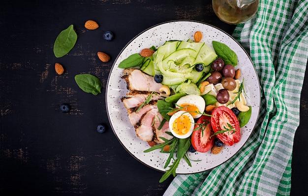 Dieta ketogeniczna. brunch keto. jajko na twardo, stek wieprzowy i oliwki, ogórek, szpinak, ser brie, orzechy i pomidor. widok z góry