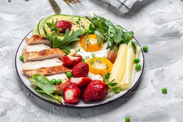 Dieta ketogeniczna. jajko sadzone, awokado, truskawka, grillowany filet z kurczaka, ser, orzechy i rukola, śniadanie niskowęglowodanowe o wysokiej zawartości tłuszczu, widok z góry,