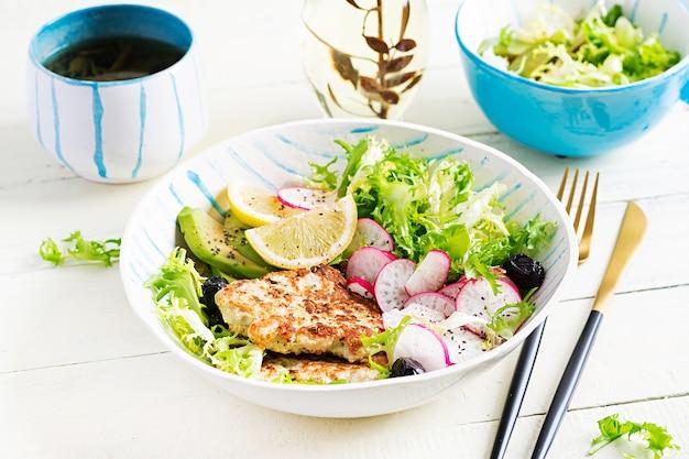 Dieta ketogeniczna. miska buddy z burgerem z kurczaka, awokado, rzodkiewką i czarnymi oliwkami. detox i zdrowa koncepcja. jedzenie keto.