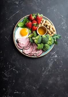 Dieta ketogeniczna o niskiej zawartości węglowodanów, widok z góry, miejsce na tekst. talerz na kamiennym czarnym tle z keto żywności: jajko, mięso, oliwa z oliwek, brokuły, jagody, orzechy, nasiona. zdrowe tłuszcze, czyste jedzenie na odchudzanie