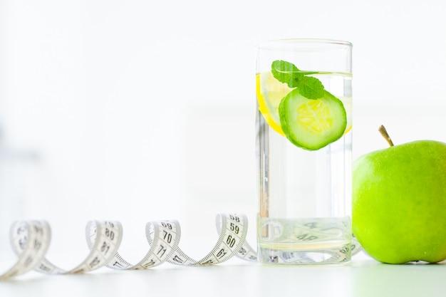 Dieta. koncepcja diety fitness i zdrowej żywności. zbilansowana dieta z owocami. świeże owoce i szklana woda, taśma miernicza