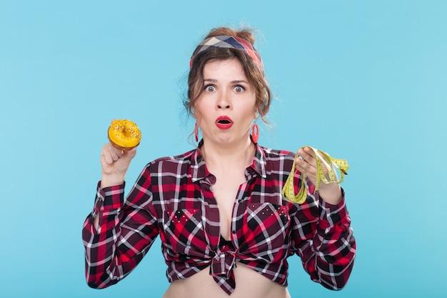 Dieta, odchudzanie i fast foody - kobieta pin-up wybierająca między deserem a miarką na niebieskim tle.