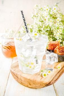 Dieta organiczna detox letni napój, napar wodny z rumiankiem i miodem, na białym drewnianym stole, z kwiatami rumianku i miodem w słoiku. skopiuj miejsce