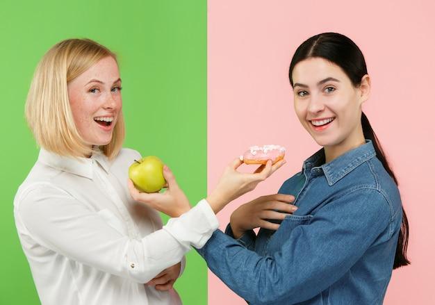 Dieta. pojęcie diety. zdrowa żywność. piękne młode kobiety wybierają między owocami i ciastem unhelathy w studio. ludzkie emocje i porównania