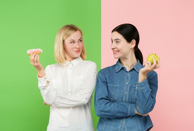 Dieta. pojęcie diety. zdrowe jedzenie. piękne młode kobiety wybierają między owocami a nieprzyjemnym ciastem