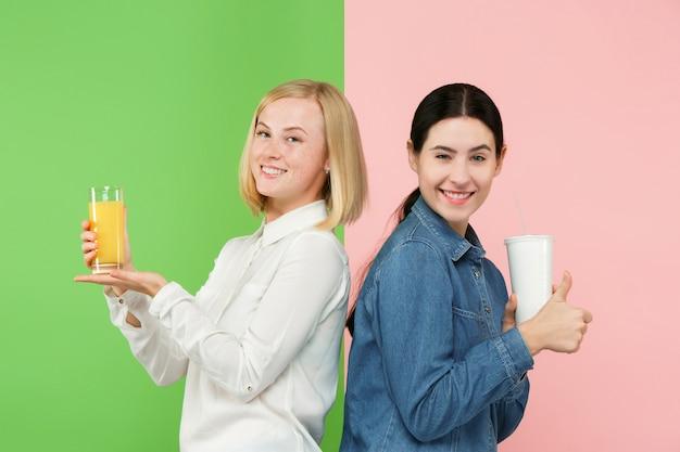 Dieta. pojęcie diety zdrowe jedzenie. piękne młode kobiety wybierają między owocowym sokiem pomarańczowym a niegodziwym gazowanym słodkim napojem