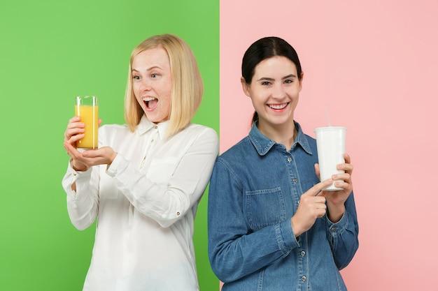 Dieta. pojęcie diety. zdrowe jedzenie. piękne młode kobiety wybierają między sokiem owocowo-pomarańczowym a nieprzyjemnym gazowanym słodkim napojem