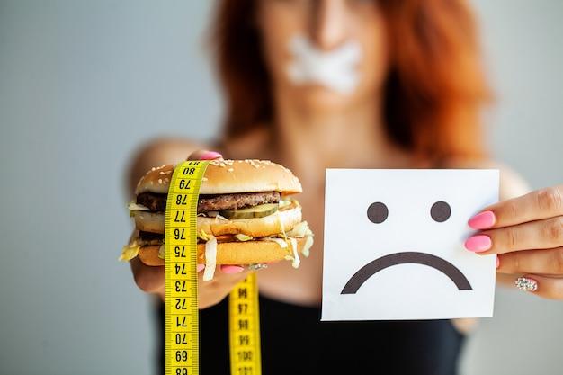 Dieta, portretowa kobieta chce zjeść burgera, ale ma zablokowane usta skochem,