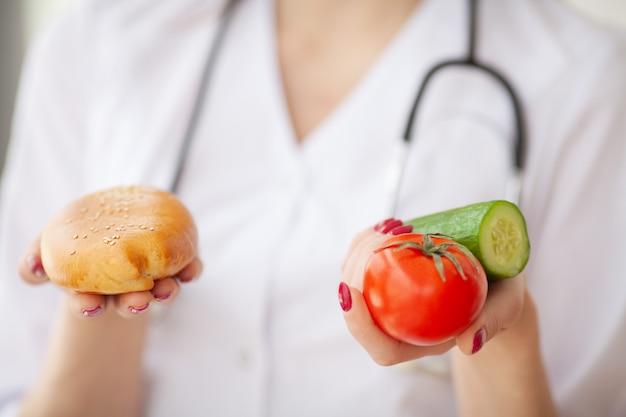 Dieta. zbliżenie na doktorskiej kobiecie daje wyborowi między pasztecikiem i świeżymi warzywami