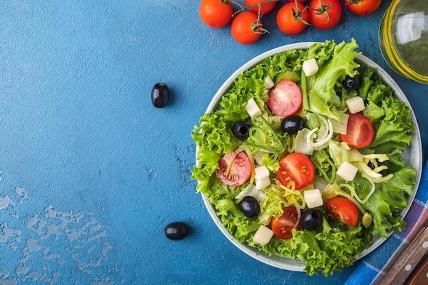 Dieta zdrowa sałatka z zieleniną, pomidorkami koktajlowymi, cebulą, serem i czarnymi oliwkami