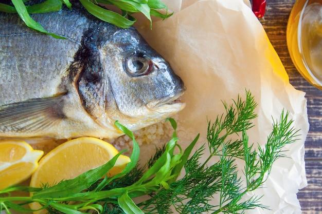 Dietetyczna dorada morska przygotowana do pieczenia z cytryną i świeżymi ziołami