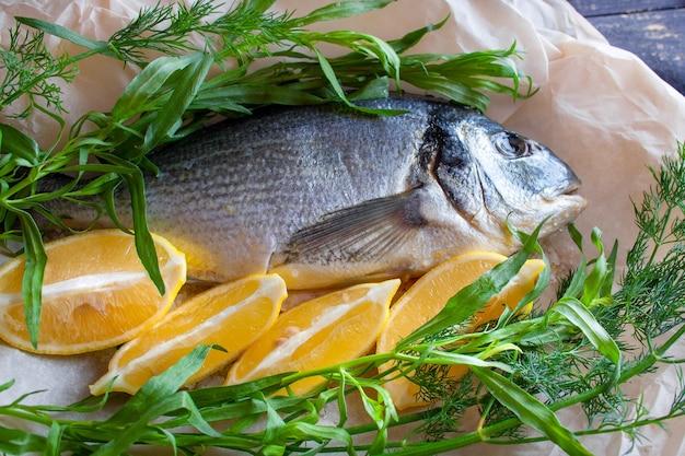 Dietetyczna dorada morska przygotowana do pieczenia z cytryną i ziołami