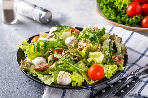 Dietetyczna i zdrowa sałatka z pomidorami, serem mozzarella, rukolą i orzechami włoskimi