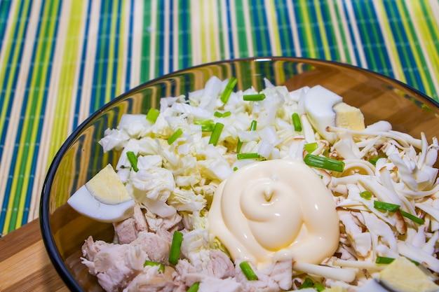 Dietetyczna sałatka do prawidłowego odżywiania z kurczakiem i jajkami na zielonej macie.