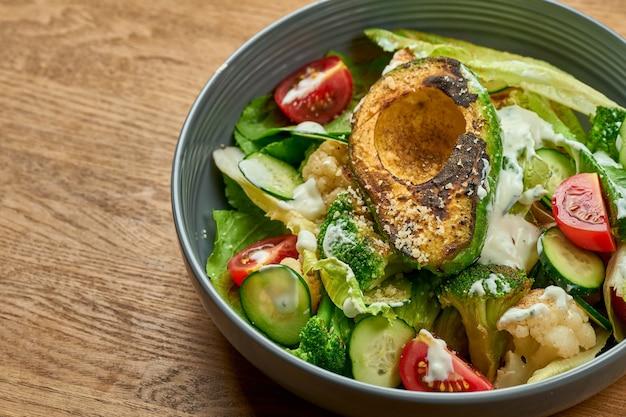 Dietetyczna sałatka z grillowanym awokado, białym sosem i warzywami w misce na drewnianym tle z szumem ziarna