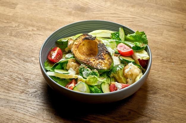 Dietetyczna sałatka z grillowanym awokado, białym sosem i warzywami w misce na drewnianym tle