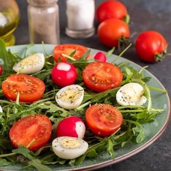 Dietetyczna sałatka z rzodkiewką, pomidorami, jajkiem przepiórczym i rukolą. koncepcja zdrowej żywności.