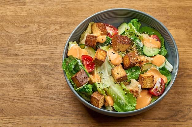 Dietetyczna sałatka ze smażonym tofu, żółtym sosem i warzywami w misce na drewnianym tle