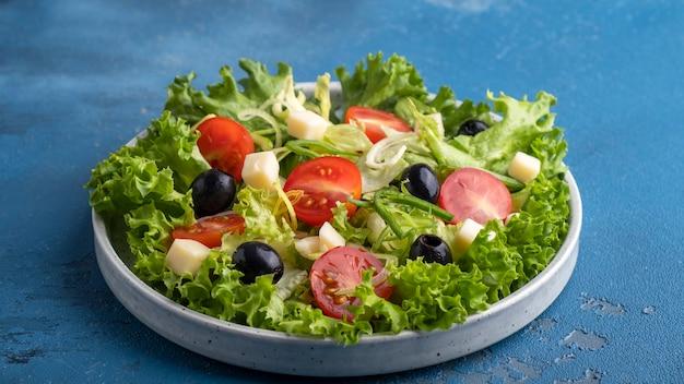 Dietetyczna zdrowa sałatka z zieleniną, pomidorkami koktajlowymi. cebula, ser i czarne oliwki. koncepcja zdrowego wegetariańskiego posiłku.