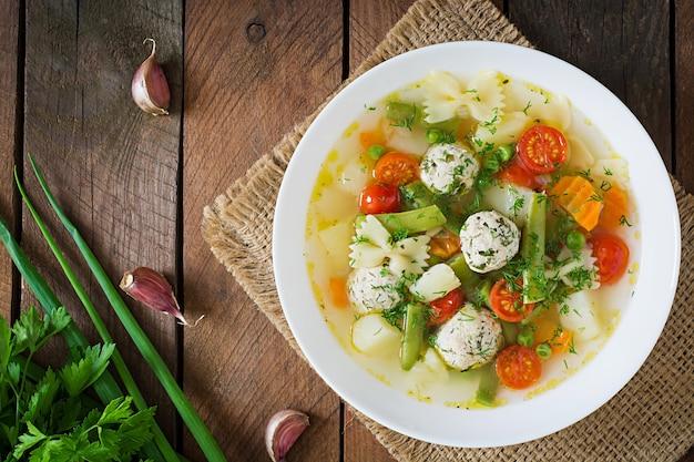 Dietetyczna zupa jarzynowa z klopsikami z kurczaka i świeżymi ziołami w drewnianej misce